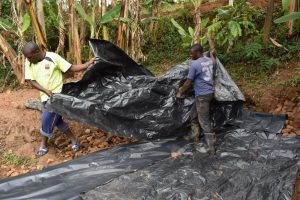 The Water Project:  Fitting The Tarp Over Backfilled Area