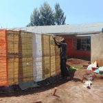 The Water Project: Kitagwa Secondary School -  Tying Sugar Sacks To Wire Walls