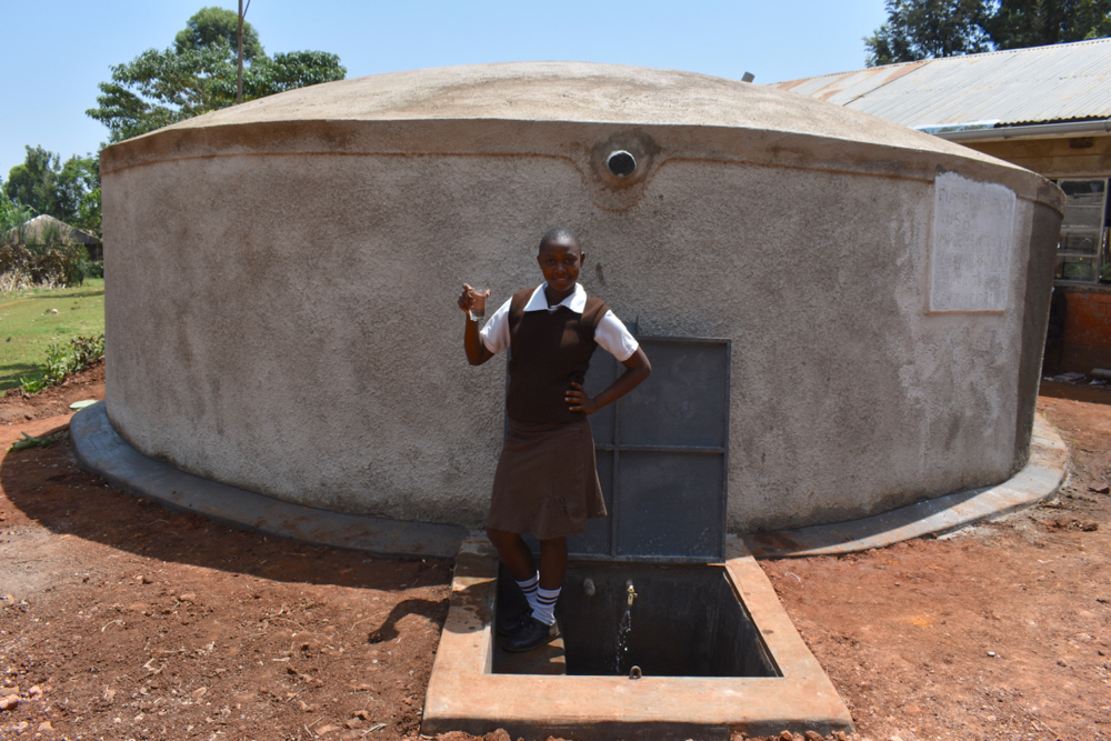 The Water Project : kenya21215-posing-with-a-clean-drink-from-the-tank