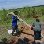 The Water Project: Kalenda A Community, Moro Spring -  Raising The Poles For Fencing