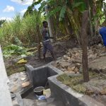 The Water Project: Kalenda A Community, Moro Spring -  Backfilling With Stones