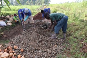The Water Project:  Community Members Help Mix Concrete