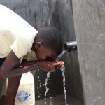 The Water Project: Kalenda A Community, Moro Spring -  Faith Enjoys A Sip Of Clean Water