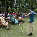 The Water Project: Kalenda A Community, Moro Spring -  Trainer Ian Leads The Physical Distancing Test