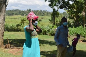 The Water Project:  A Woman Demonstrates How To Properly Put On A Mask