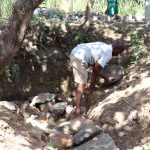 The Water Project: Luyeshe Community, Khausi Spring -  Backfilling Using Large Stones