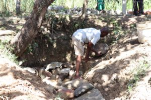 The Water Project:  Backfilling Using Large Stones