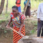 The Water Project: Luyeshe Community, Khausi Spring -  Madam Miriam Shoveling Concrete