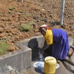 The Water Project: Indulusia Community, Osanya Spring -  Mama Osanya Enjoying Clean Flowing Water
