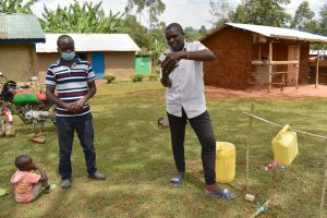 The Water Project:  Trainer Victor Watches A Man Practice Handwashing