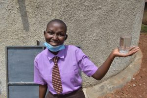 The Water Project:  Brendah Holds A Cup Of Clean Water From The Tank