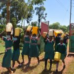 The Water Project: Itieng'ere Primary School -  Students Carrying Water