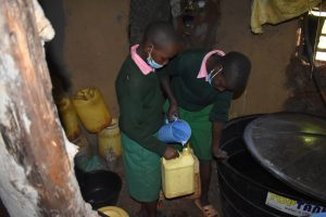 The Water Project:  Collecting Water From A Nearby Home