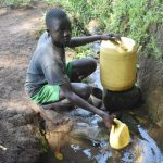 The Water Project: Emusaka Community, Manasses Spring -  Tyrone Collecting Water