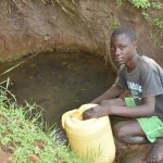 The Water Project: Emusaka Community, Manasses Spring -  Tyrone Fetching Water