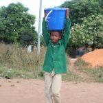 The Water Project: Kulafai Rashideen Primary School -  Student Carrying Water