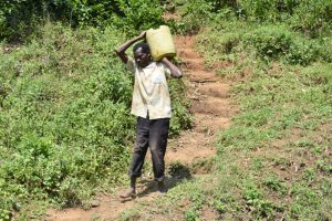 The Water Project:  Community Member Carrying Materials To Spring Site