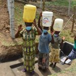 The Water Project: Mukoko Community, Zebedayo Mutsotsi Spring -  Women Carrying Their Clean Water Home