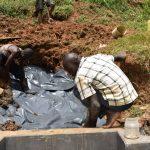 The Water Project: Mushikulu B Community, Olando Spring -  Laying The Plastic Tarp