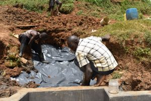 The Water Project:  Laying The Plastic Tarp