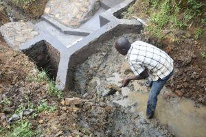 The Water Project:  Reinforcing The Headwall With Clay For Better Water Collection