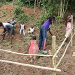 The Water Project: Emutetemo Community, Lubale Spring -  Planting Grass Above Catchment Area