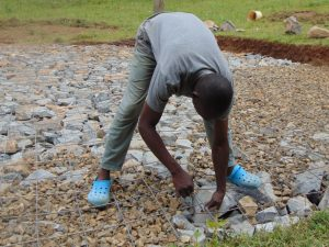 The Water Project:  Filling Excavated Area With Stones And Wire