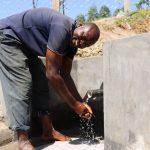 The Water Project: Elwichi Community, Mulunda Spring -  Mark Wamondo Washing Hands