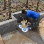 The Water Project: Isanjiro Community, Musambai Spring -  Collecting Water