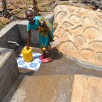 The Water Project: Isanjiro Community, Musambai Spring -  Mercy Collecting Water