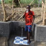 The Water Project: Mukhuyu Community, Gideon Kakai Chelagat Spring -  Enoc Drinking Water From The Spring