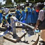 The Water Project: Ibokolo Primary School -  A Parent Pumping Water From The Borehole