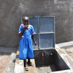 The Water Project: Gidimo Primary School -  Enjoying Water From The Tank