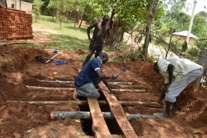 The Water Project:  Laying Poles To Support Latrine Foundation