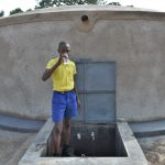 The Water Project: Jimarani Primary School -  Pupil Drinking Water From The Rain Tank
