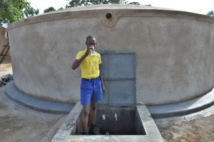 The Water Project:  Pupil Drinking Water From The Rain Tank