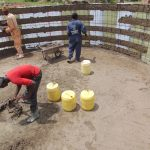 The Water Project: Kitambazi Primary School -  Applying The First Layer Of Concrete