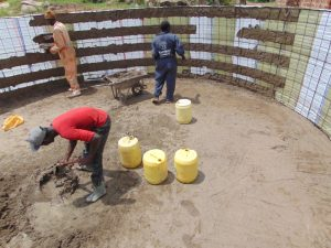 The Water Project:  Applying The First Layer Of Concrete