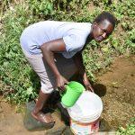 The Water Project: Emuyere Community, Kaikai Spring -  Selpher Muchenya Fetching Water
