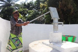 The Water Project:  Woman Pumps The Well