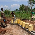 The Water Project: Alero B Community -  Margret Nambuya Speaks With The Well Caretaker