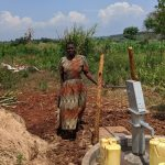 The Water Project: Alero B Community -  Margret Nambuya Standing Next To New Drilled Borehole