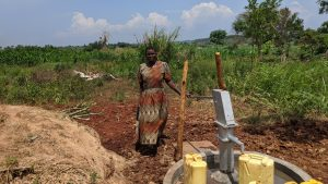 The Water Project:  Margret Nambuya Standing Next To New Drilled Borehole
