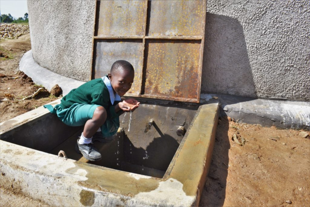 The Water Project : kenya21209-a-pupil-drinking-water-from-the-water-point-2