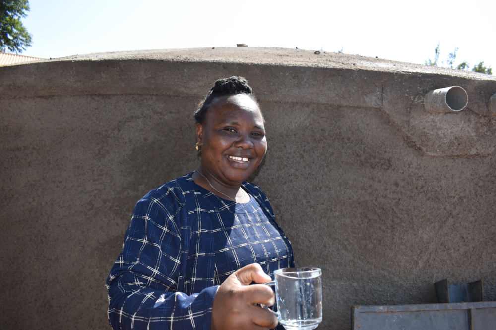 The Water Project : kenya21229-madam-eunice-happy-with-water-from-the-tank-1-2
