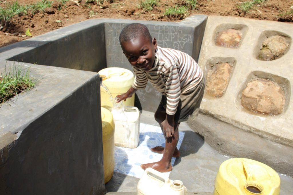 The Water Project : kenya21037-patel-drawing-water-at-protected-spring