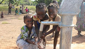 Girls play in clean, safe water from a new well in Burkina Faso.