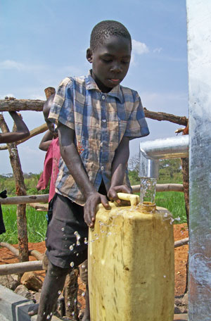Boy filling jerry can at his new well